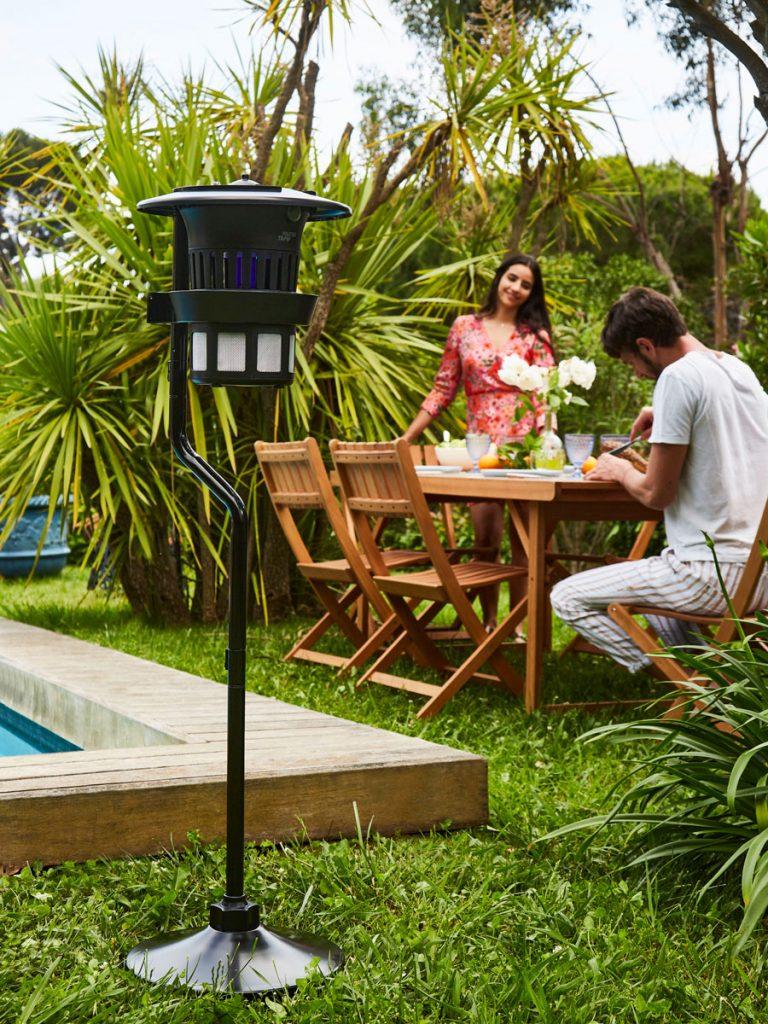Lampe anti-moustiques Tiger Trap Pro placée dans un jardin au bord de la piscine